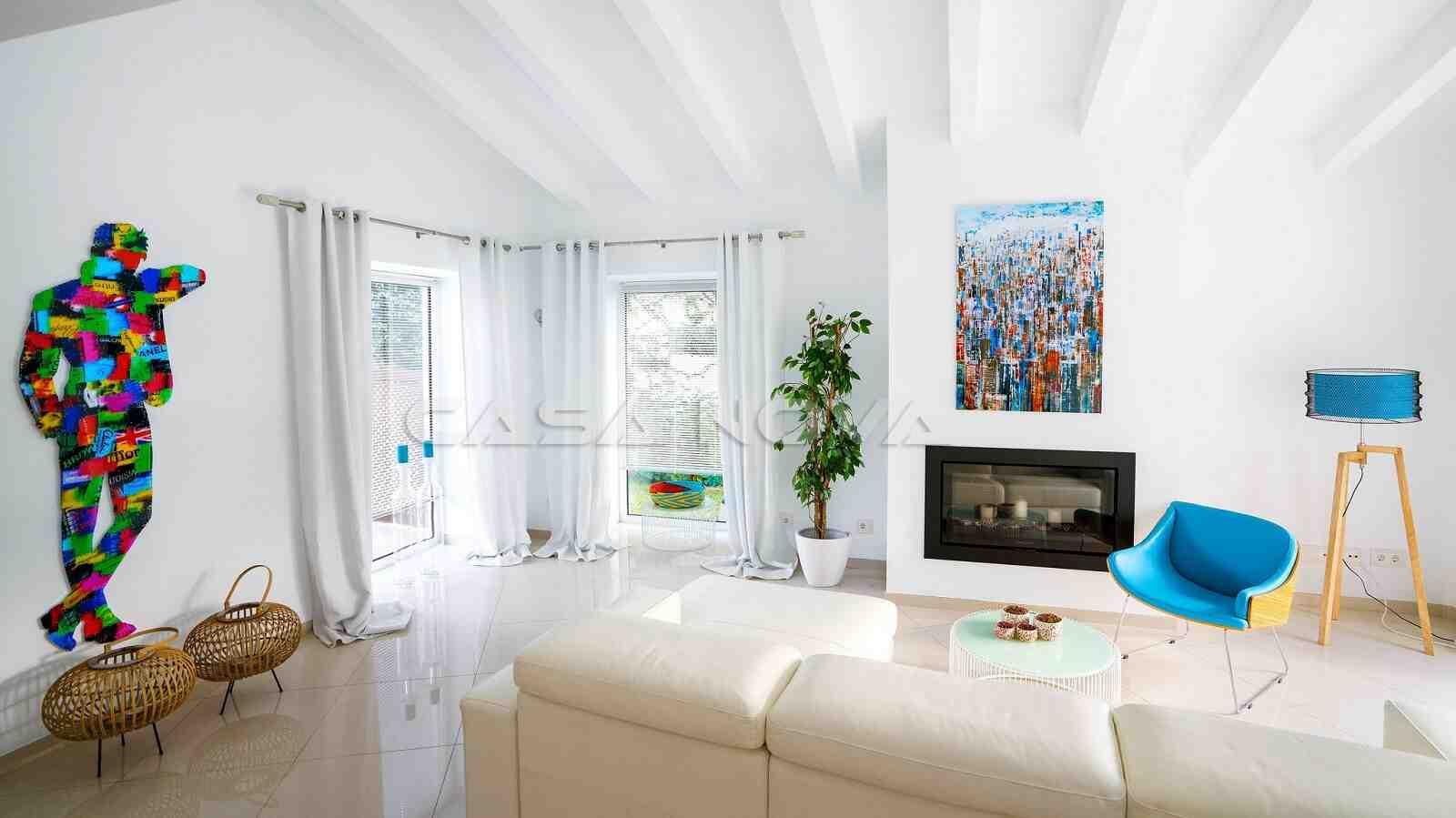 Heller Wohnraum mit Kamin und Holzbalkendecke