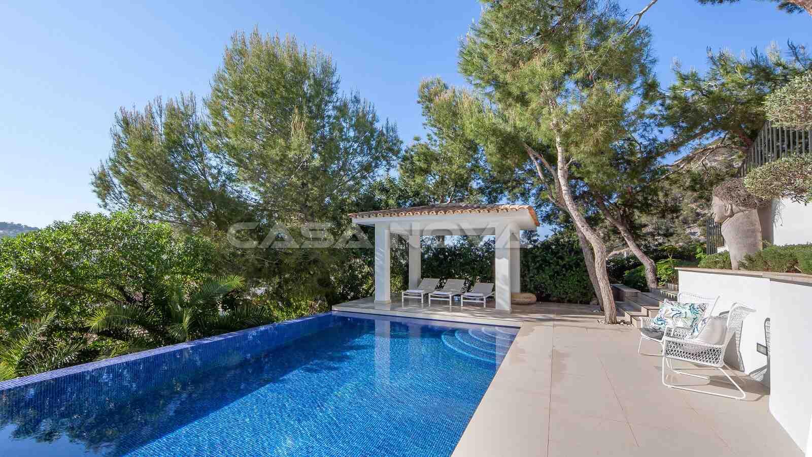 Großer Swimmingpool mit Terrasse und Poolhaus