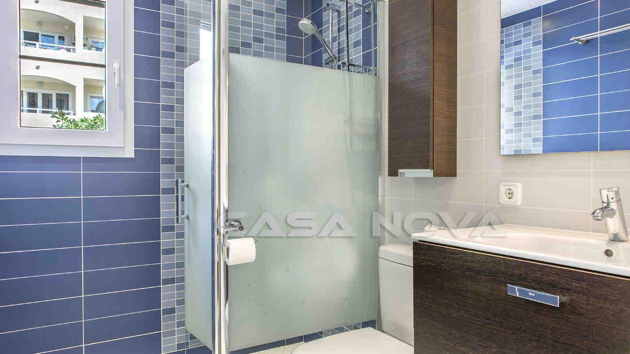Schickes Badezimmer mit Glasdusche und Fenster
